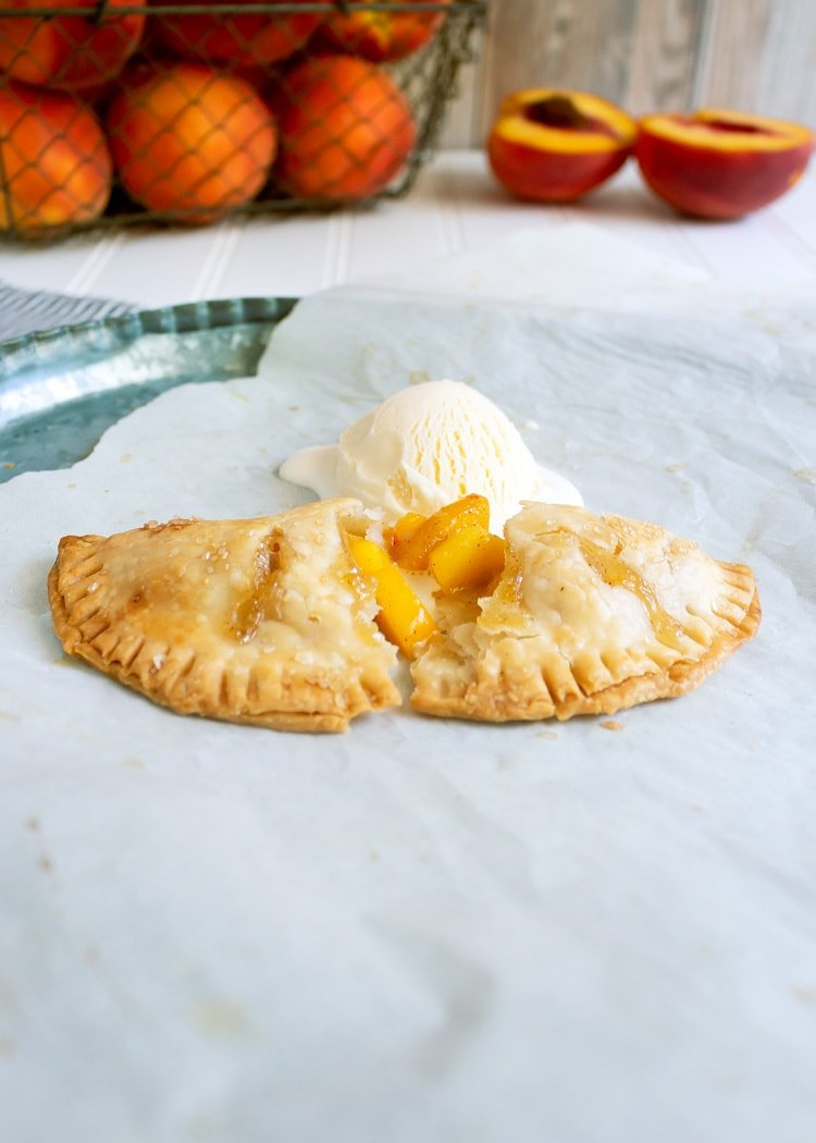 side view of peach hand pie that's been broken in half and topped with vanilla ice cream