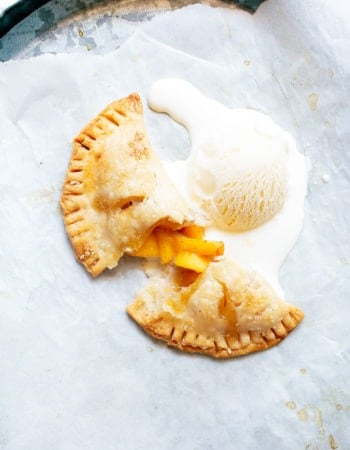 a grey platter with a cup open peach hand pie and a scoop of vanilla ice cream