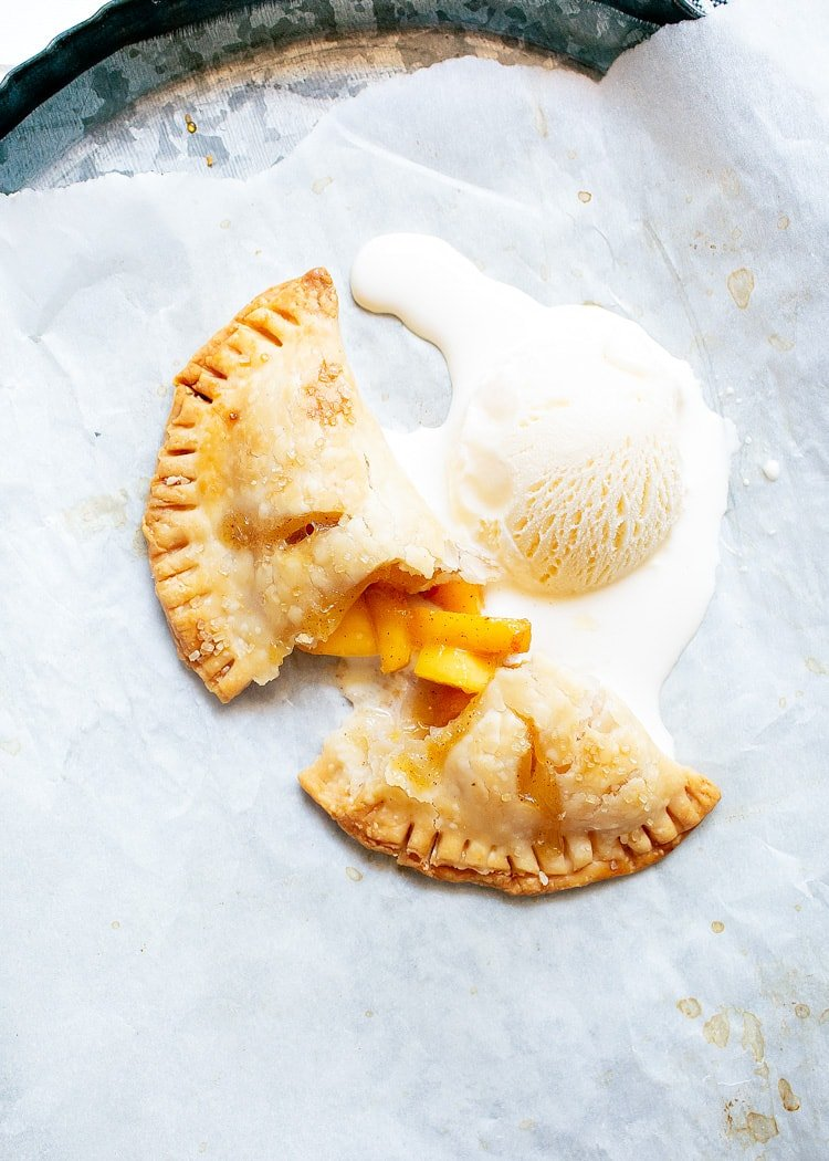 peach hand pie broken in half and topped with melting vanilla ice cream