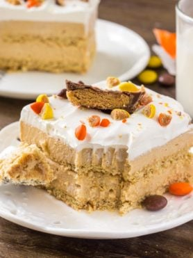 A slice of creamy peanut butter icebox cake with whipped topping and peanut butter cups.