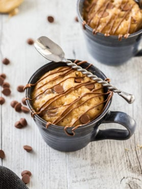Birdseye view of a mug cake in a blue mug with chocolate drizzled over the top and a spoon sitting on top