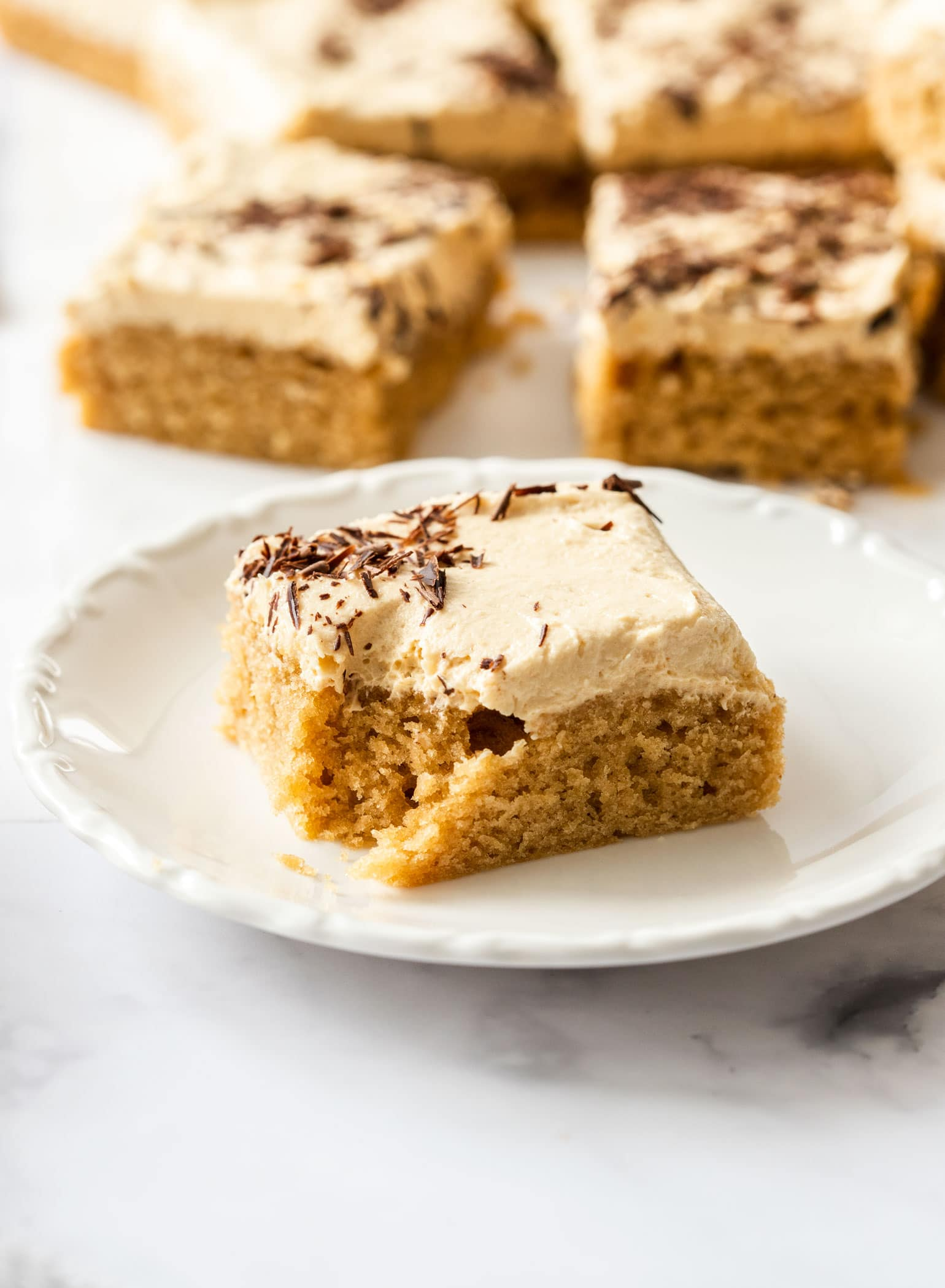 a slice of peanut butter sheet cake on a white saucer