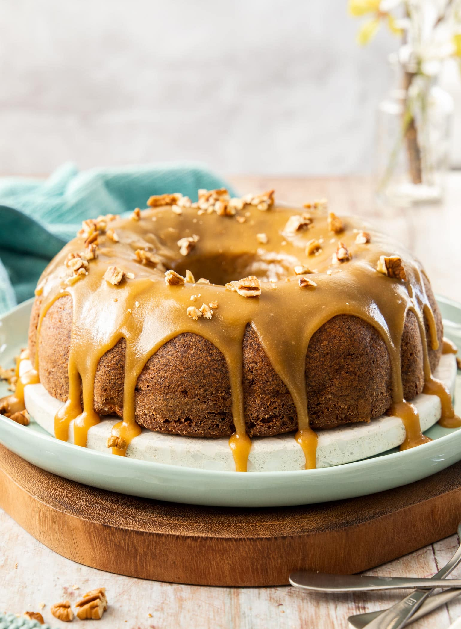 A bundt cake with caramel icing dripping down it, on a white and green platter. It sits on a wooden board