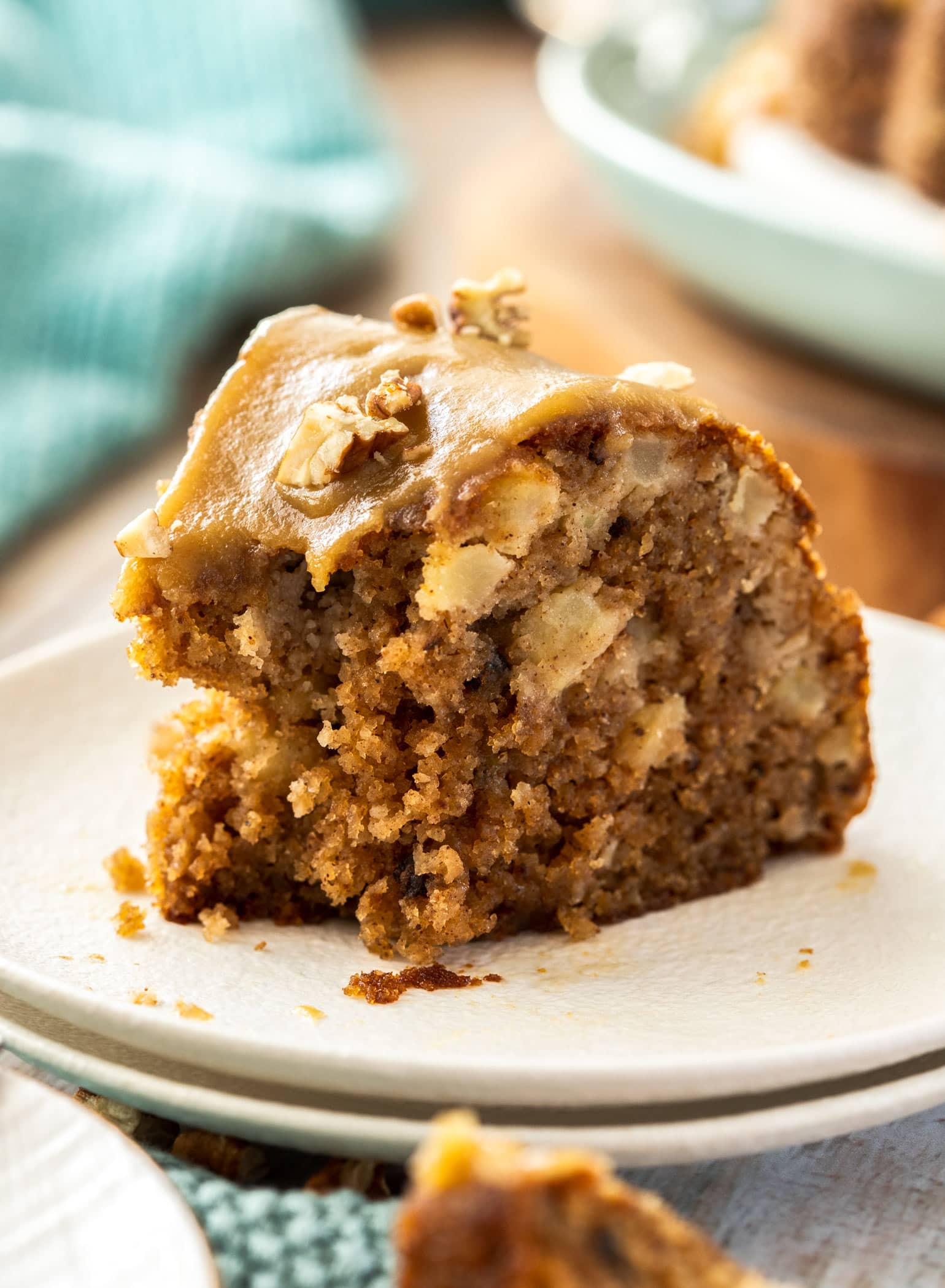 Closeup shot of a slice of apple bundt cake with a bite taken out of it