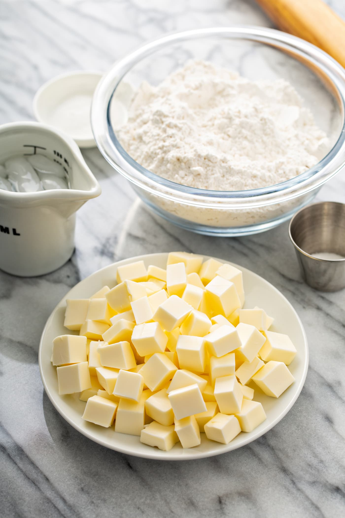 A photo of the ingredients for a perfect pie crust sitting on a table - flour, salt, ice water and small cubes of butter.