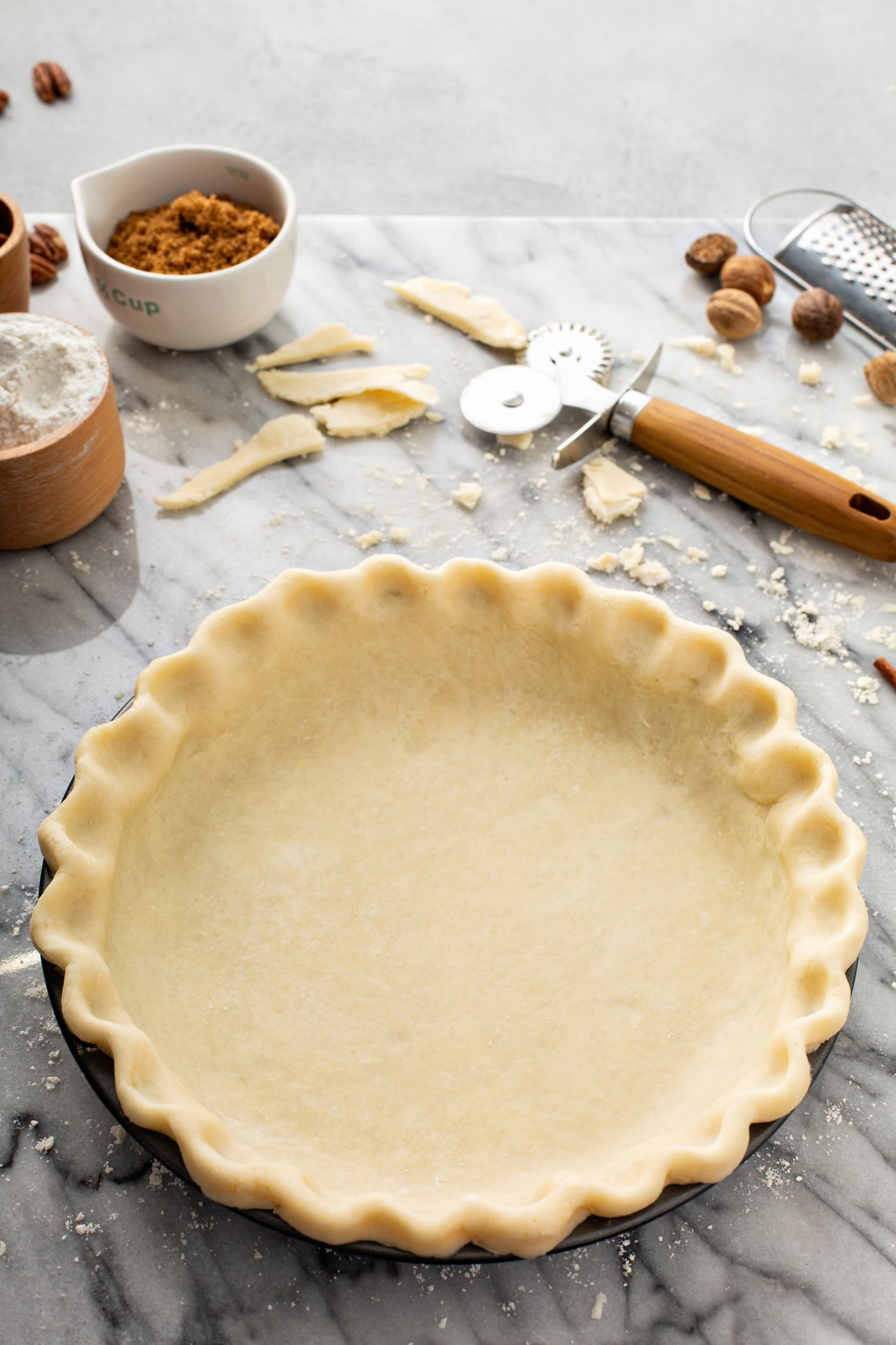 A photo of an uncooked pie crust in a pie tin sitting on a table