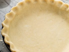 A prepared pie crust with fluted edges in a pie pan.