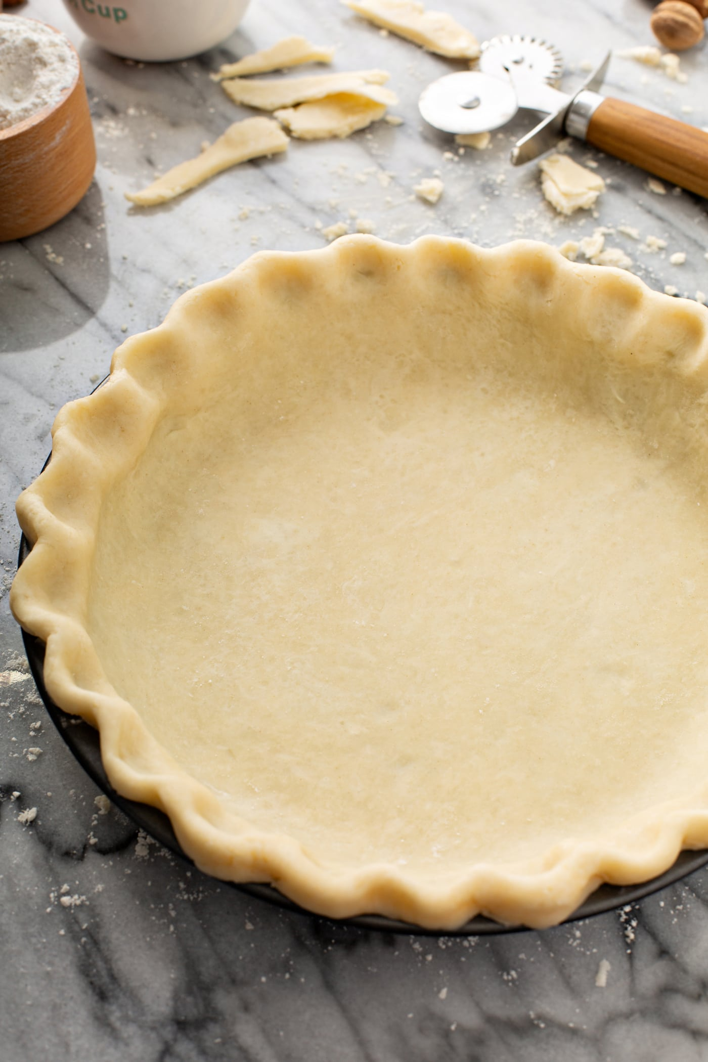 A photo of an uncooked butter pie crust in a pie tin sitting on a table.