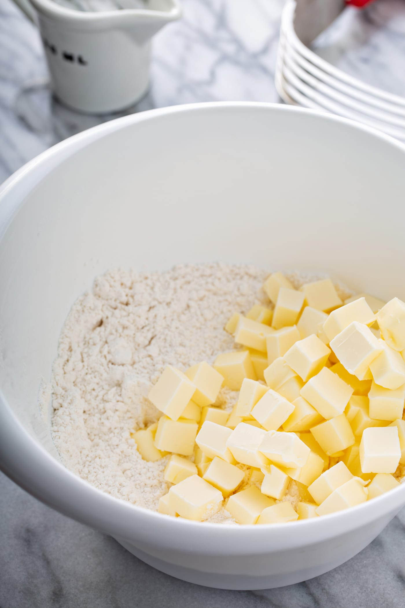 A photo of small cubes of butter piled on top of flour in a white mixing bowl.