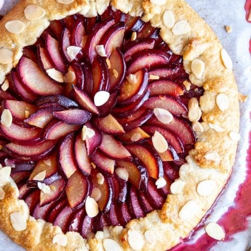 A plum galette on a baking sheet