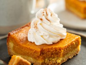 A square piece of pumpkin gooey butter cake with a swirl of whipped cream on top. A fork with a bite of cake is laying on the plate and a white cup and white plate with a piece of pumpkin cake are in the background.