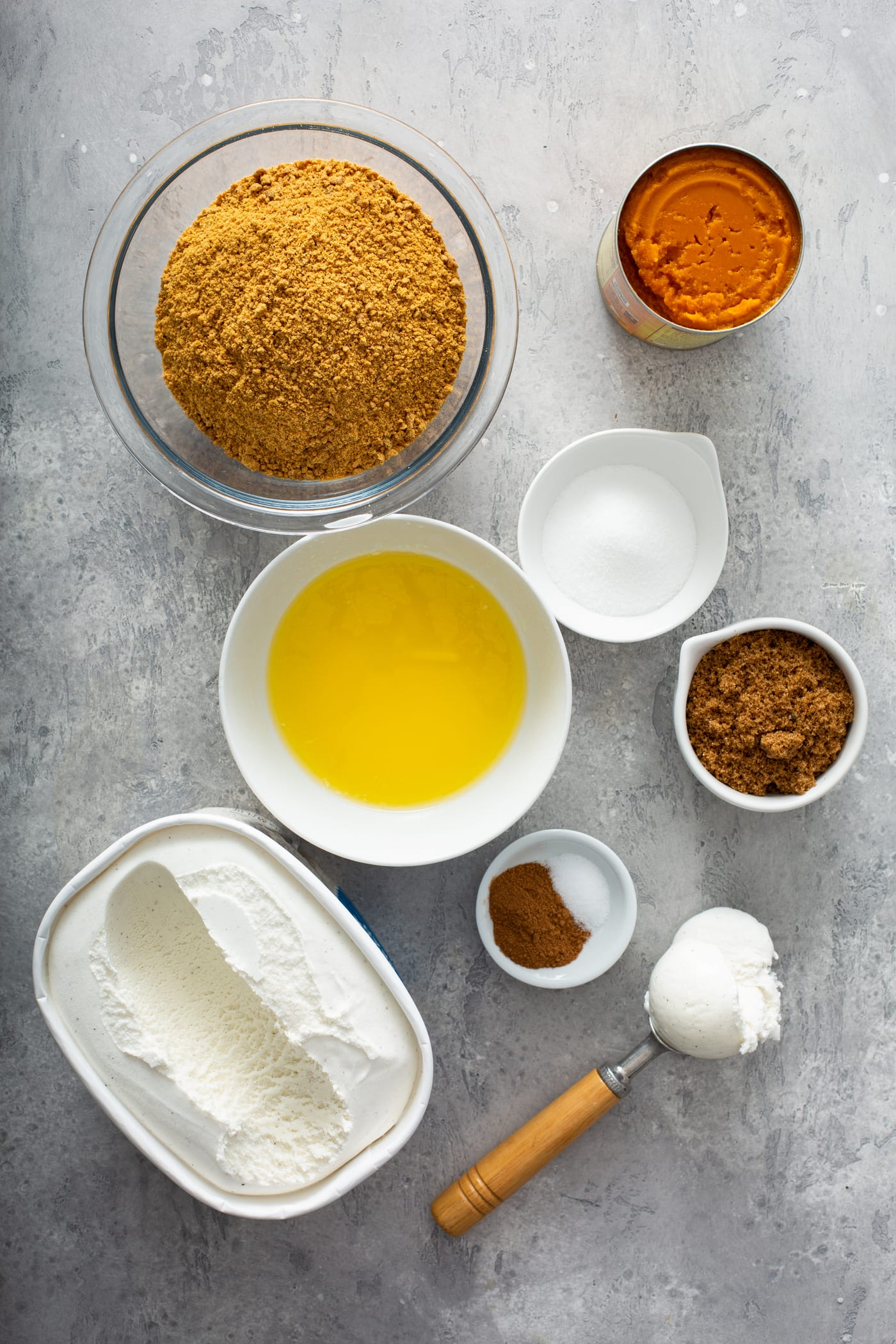 Small containers of ingredients for pumpkin ice cream pie. There are containers of pumpkin, gingersnap crumbs, butter, spices, sugar, brown sugar, and vanilla ice cream.