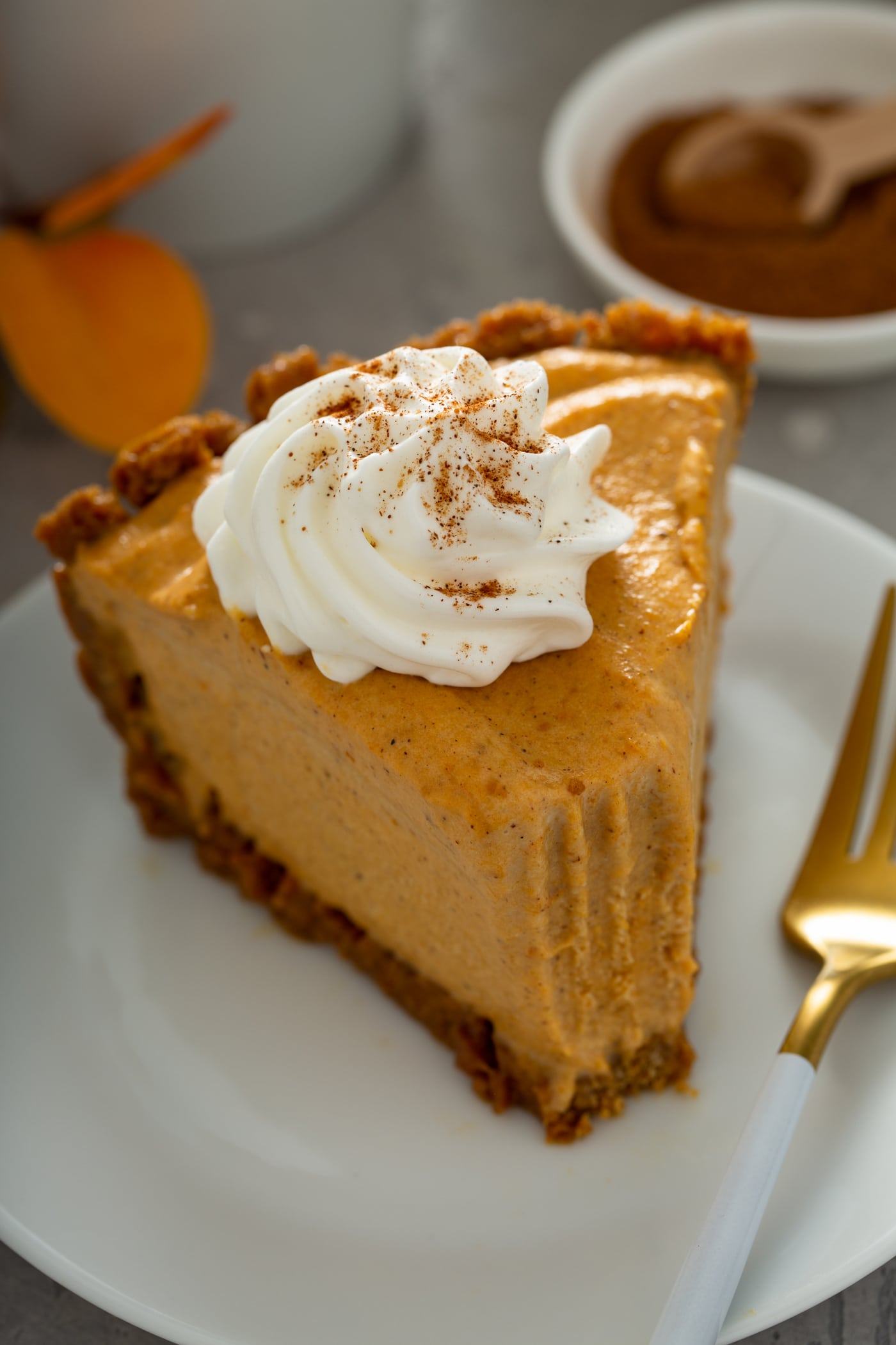 A slice of pumpkin ice cream pie with a fork next to it. A bite has been taken in the pie and it is topped with a dollop of whipped cream sprinkled with cinnamon.