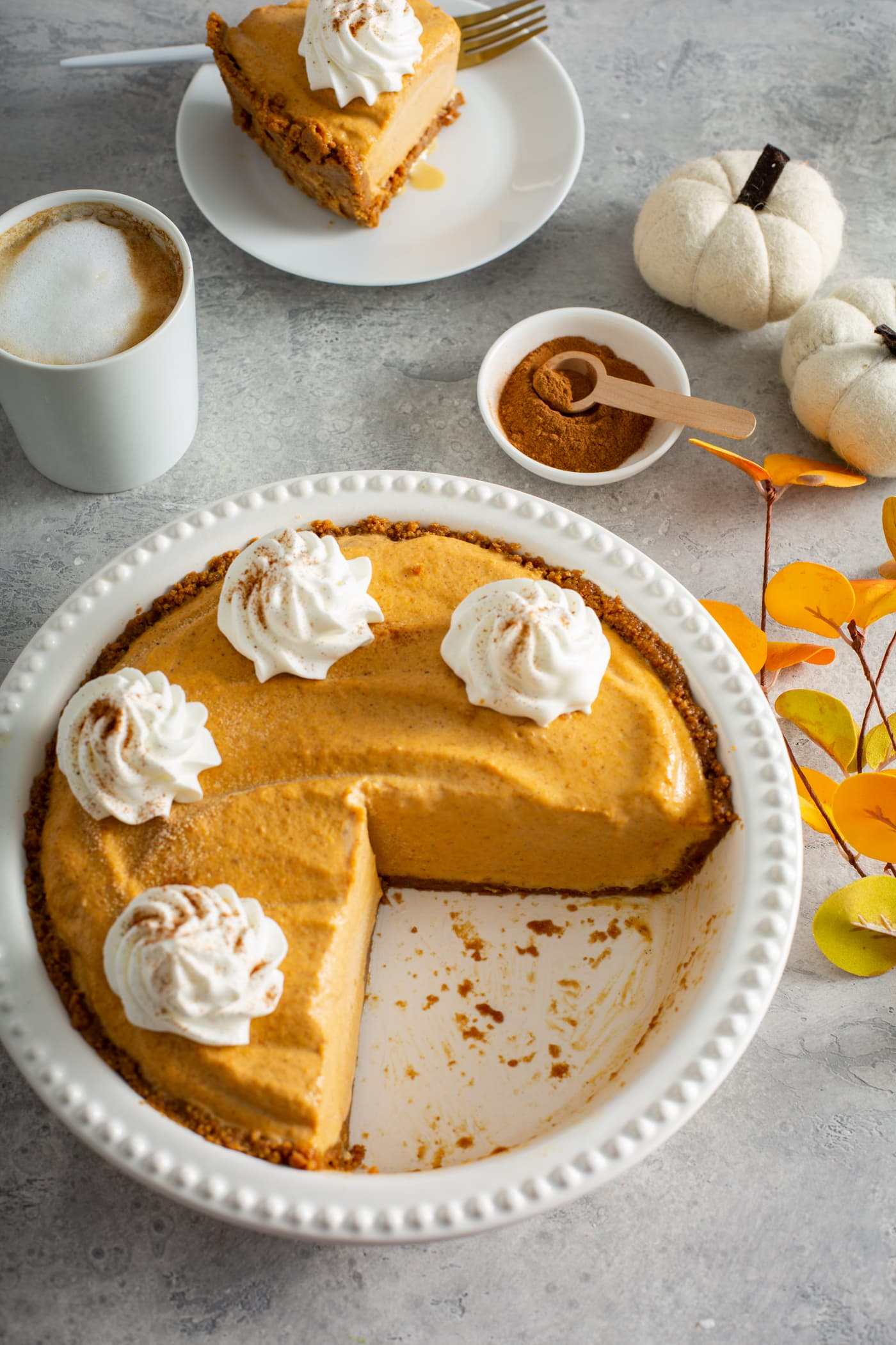 A white pie dish with part of a pumpkin ice cream pie that is topped with dollops of whipped cream sprinkled with cinnamon. There Is A white mug with a drink topped with whipped cream, a small dish with a wooden spoon filled with cinnamon, two tiny white pumpkins and a dessert plate with a slice of pie in the background.