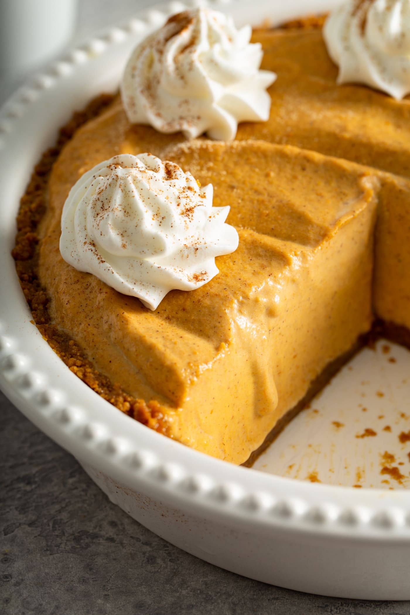 A pumpkin ice cream pie in a white pie dish with a slice removed. The pie has dollops of whipped cream sprinkled with cinnamon on top.