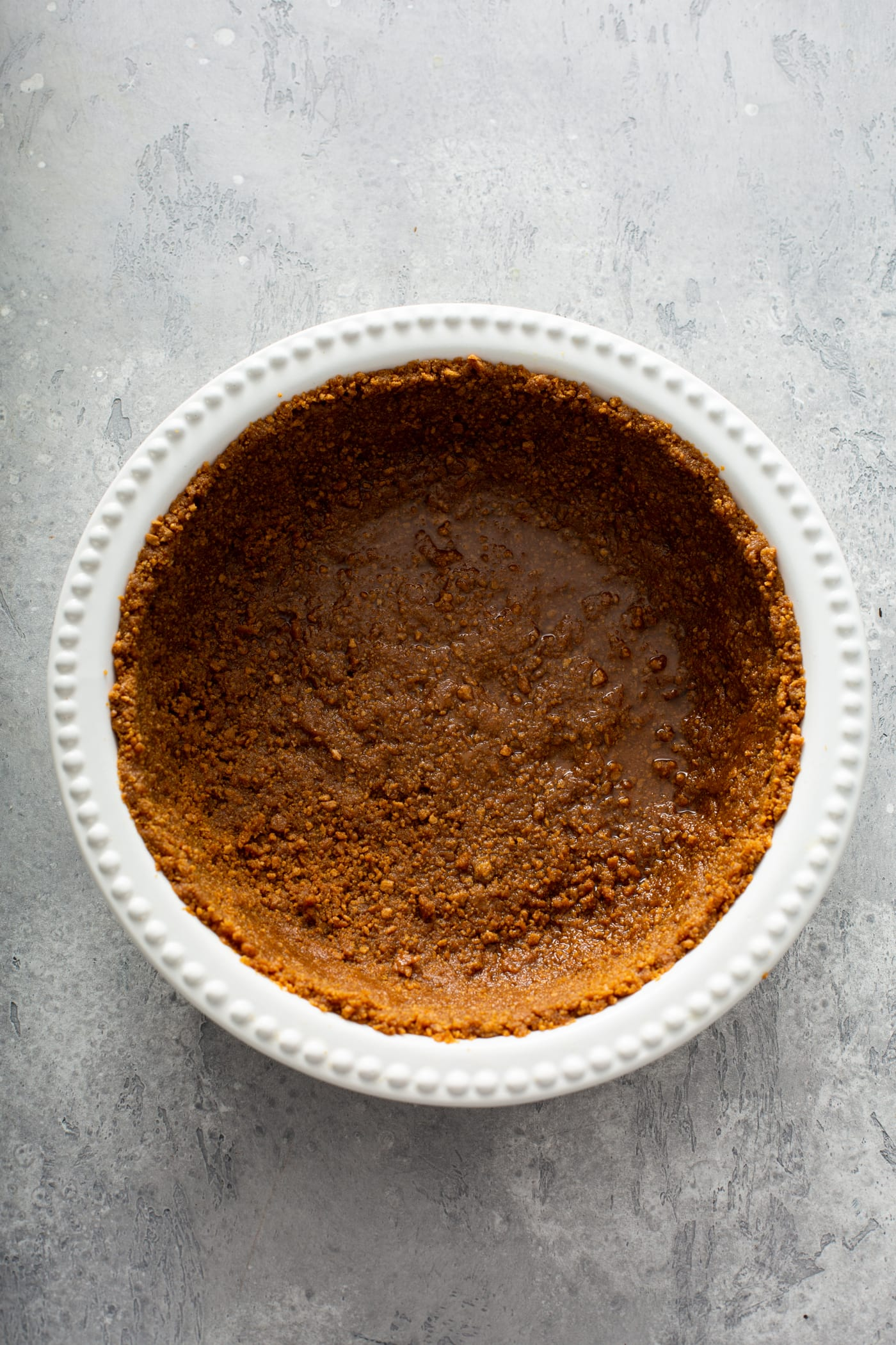 A white pie dish with a gingersnap crust in it.