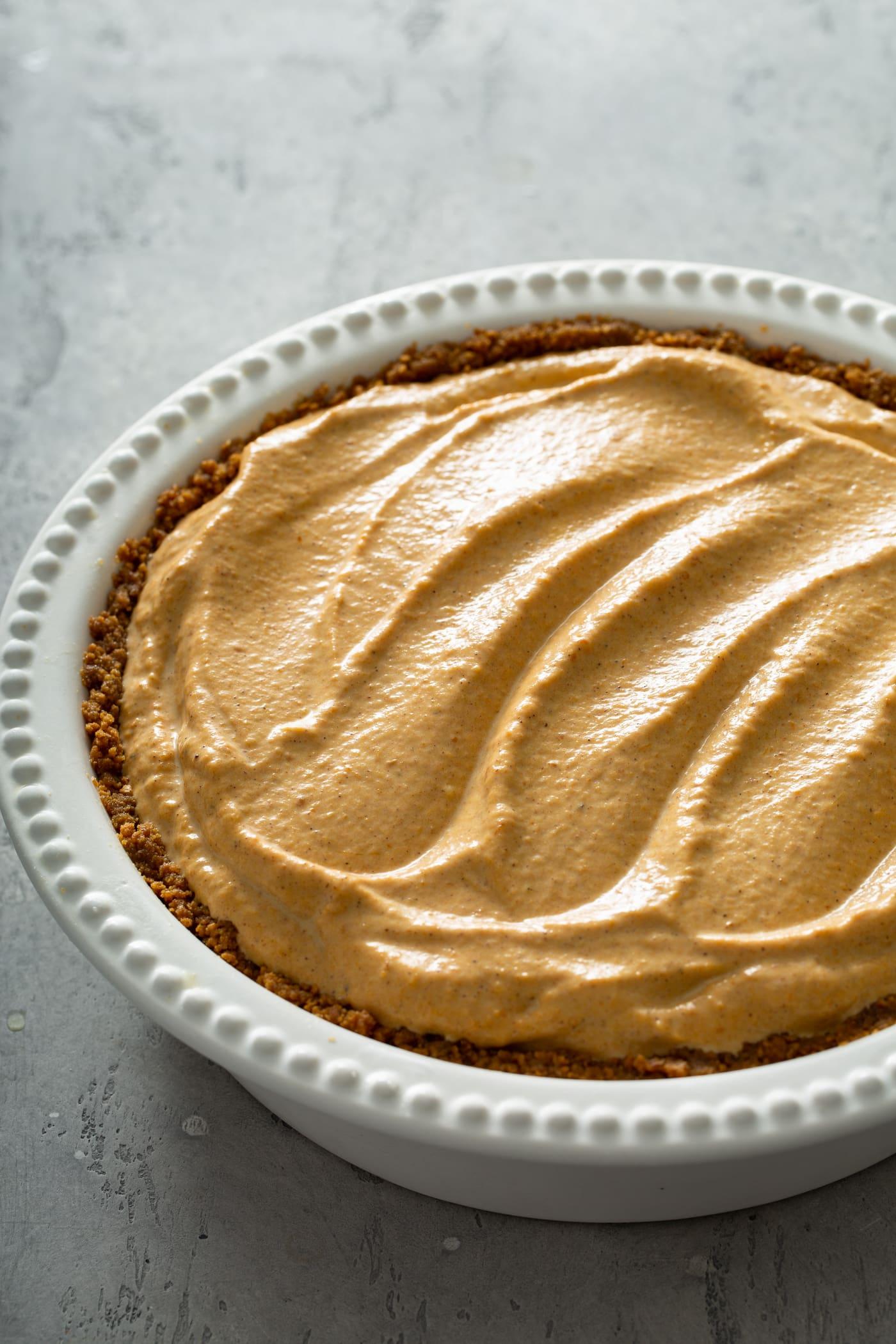 A whole pumpkin ice cream pie in a white pie dish.
