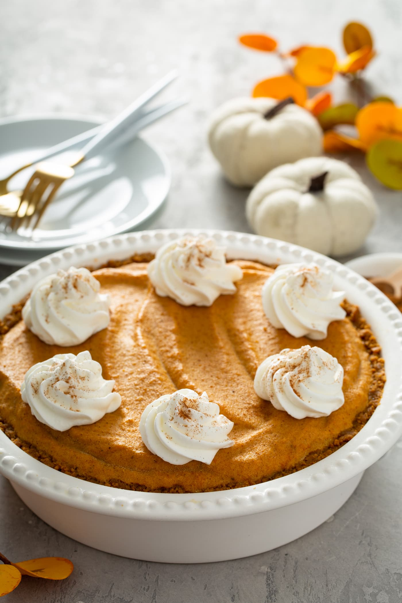 A whole pumpkin ice cream pie in a white pie dish. The pie has dollops of whipped cream sprinkled with cinnamon on top. There is a stack of white dessert plates with three forks on them, two tiny white pumpkins, and fall colored leaves behind the pie.