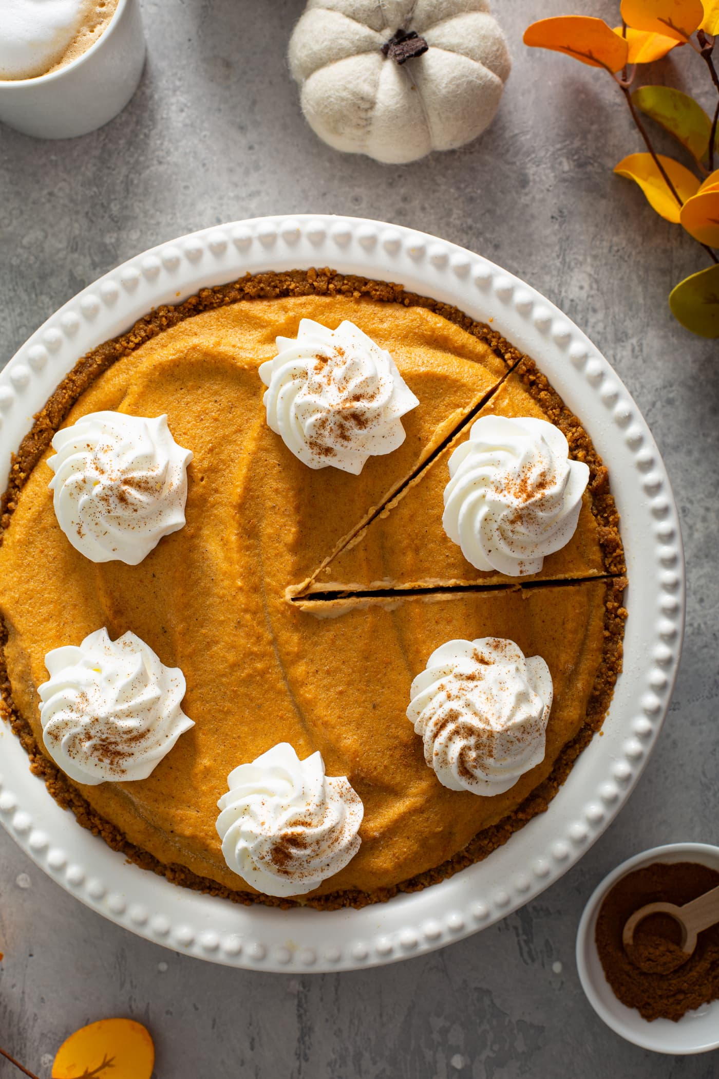 A whole pumpkin ice cream pie in a white pie dish. The pie has dollops of whipped cream sprinkled with cinnamon on top. A piece of pie has been cut but not removed from the dish. A small bowl of cinnamon, a tiny white pumpkin, and a mug of hot cocoa are in the background.