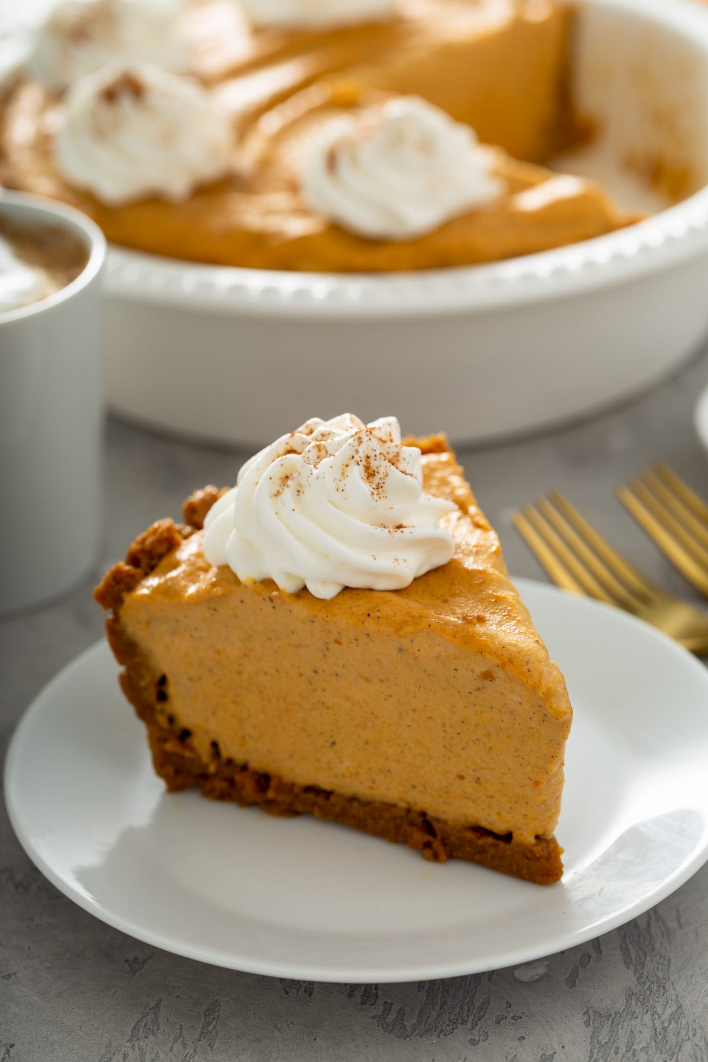 A piece of pumpkin ice cream pie on a white dessert plate. The pie has a dollop of whipped cream sprinkled with cinnamon on top. There are two forks beside the plate, and the rest of the pumpkin ice cream pie in a pie dish is in the background.