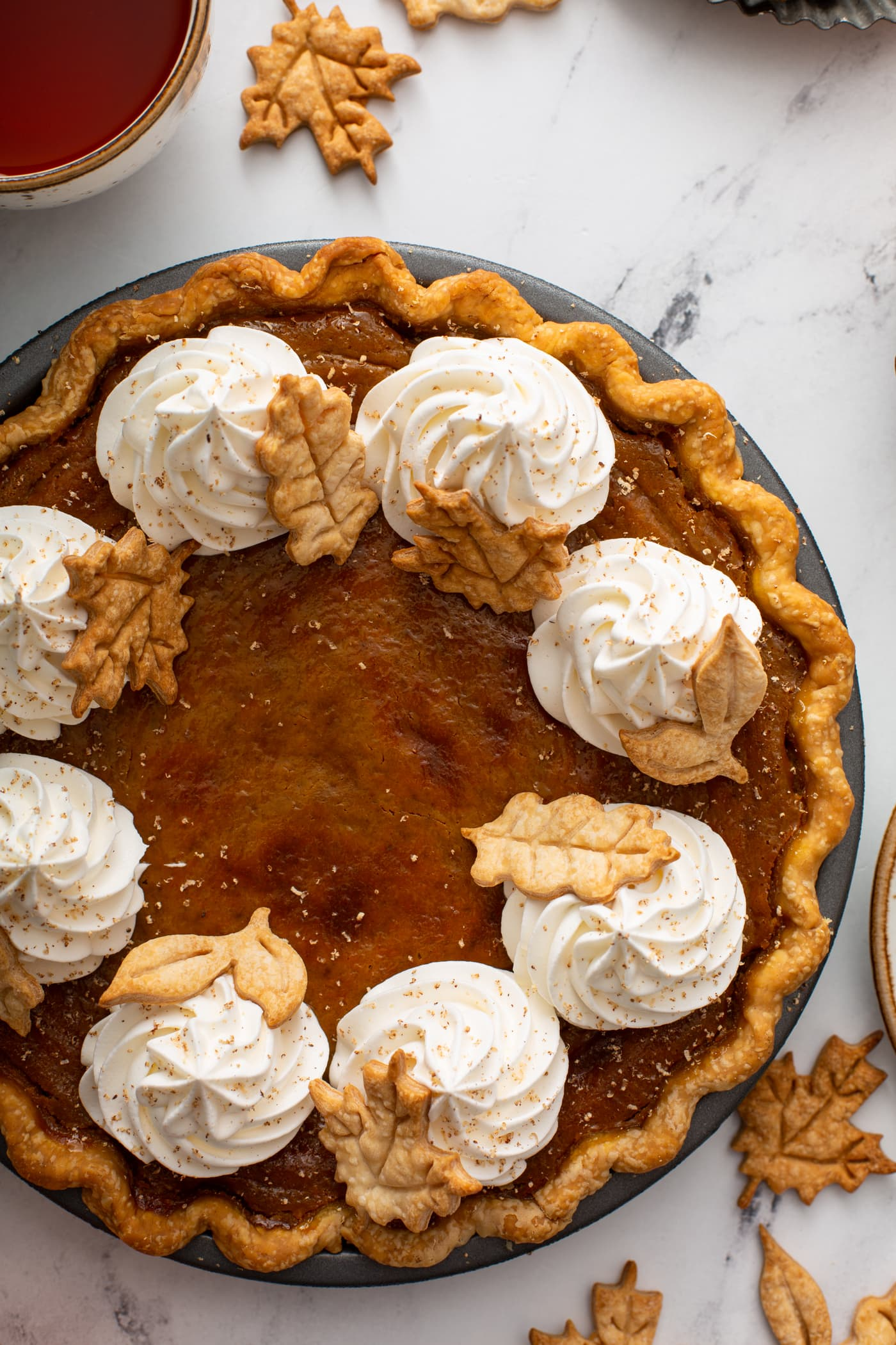 A photo of a pumpkin pie topped with piped whipped cream and stamped pie crust leaves taken from above.