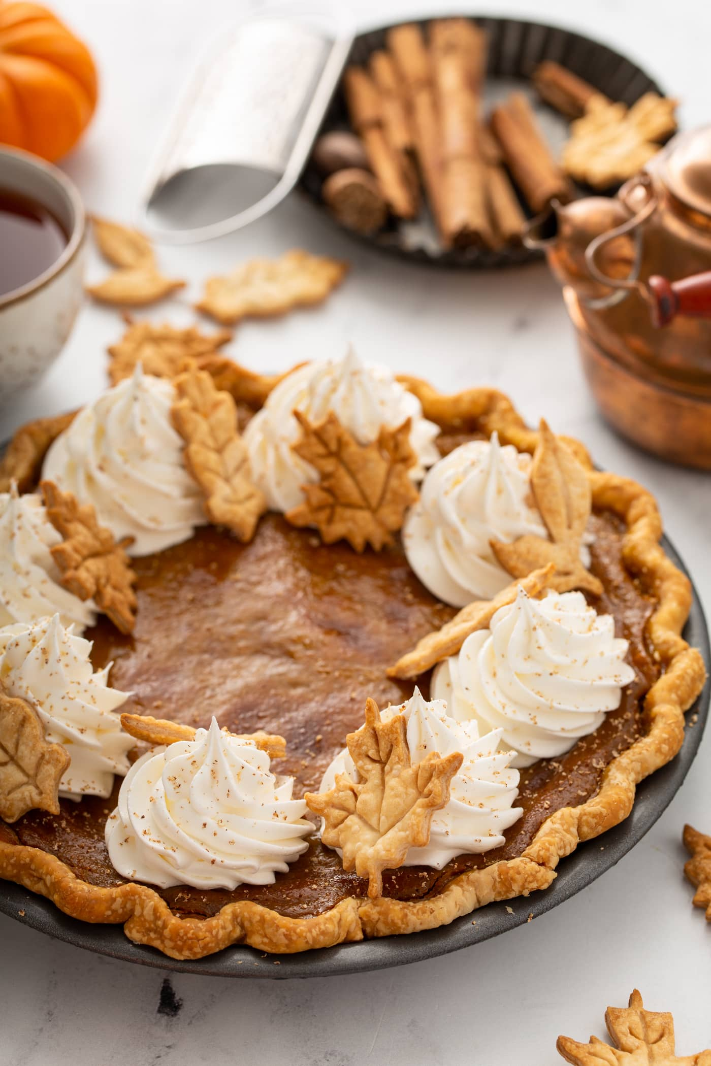 A whole pumpkin pie topped with piped whipped cream and pie crust leaves.