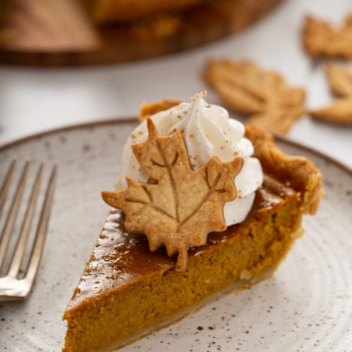 A single slice of pumpkin pie topped with piped whipped cream and a pie crust leaf.