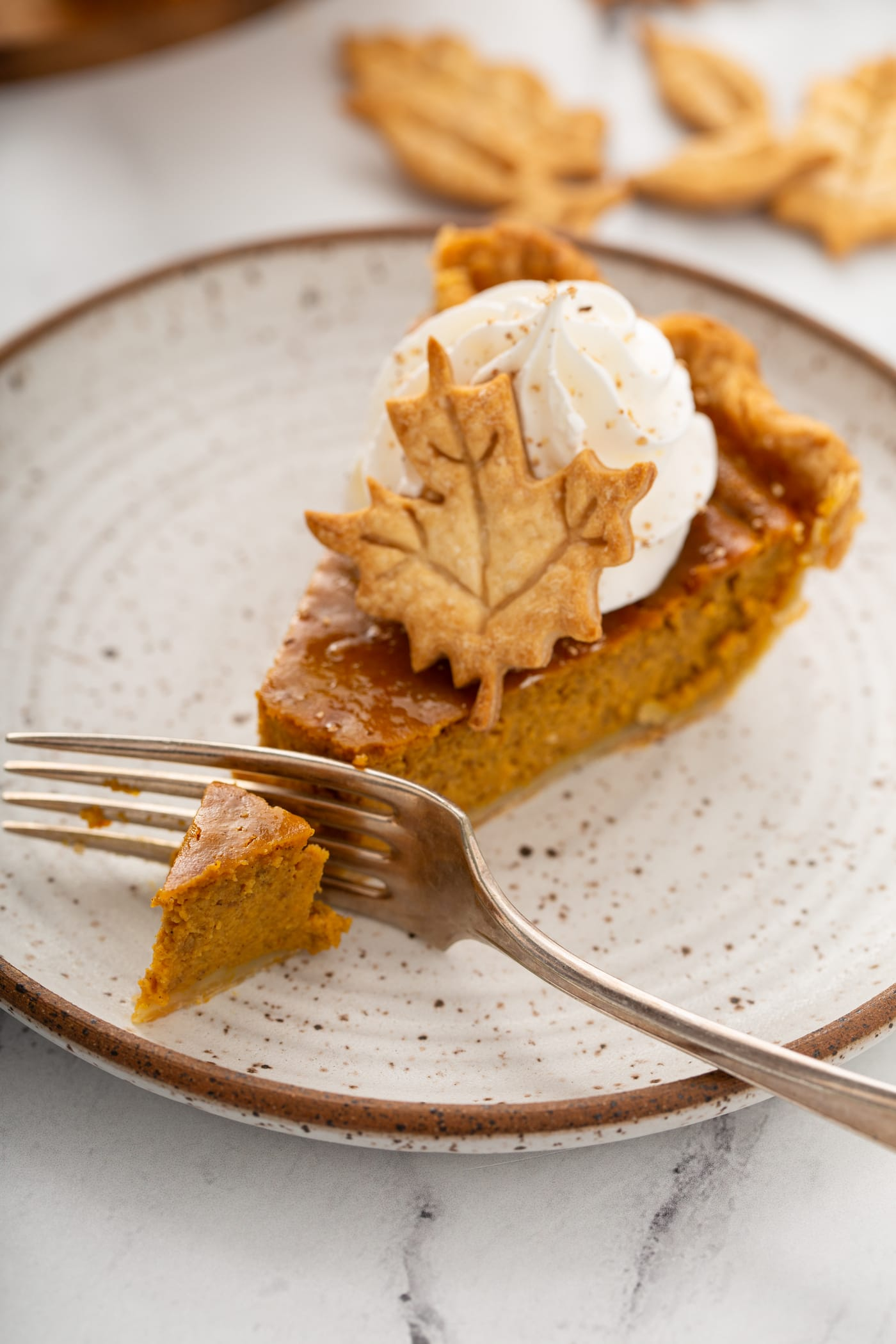 A photo of a slice of pumpking pie with a fork slicing through the end topped with piped whipped cream and a pie crust leaf.