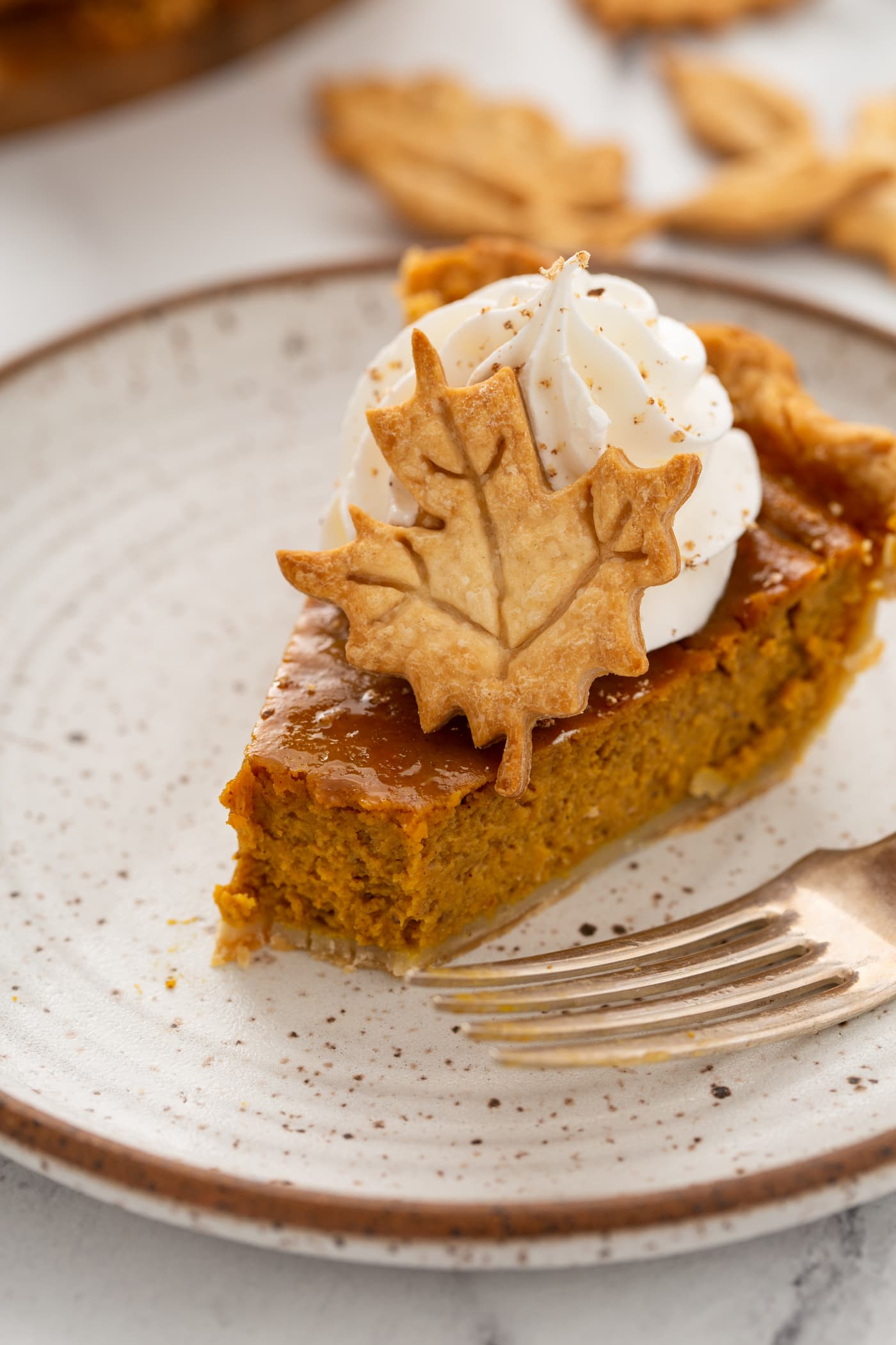 A photo of a slice of pumpking pie with a bite removed topped with piped whipped cream and a pie crust leaf.