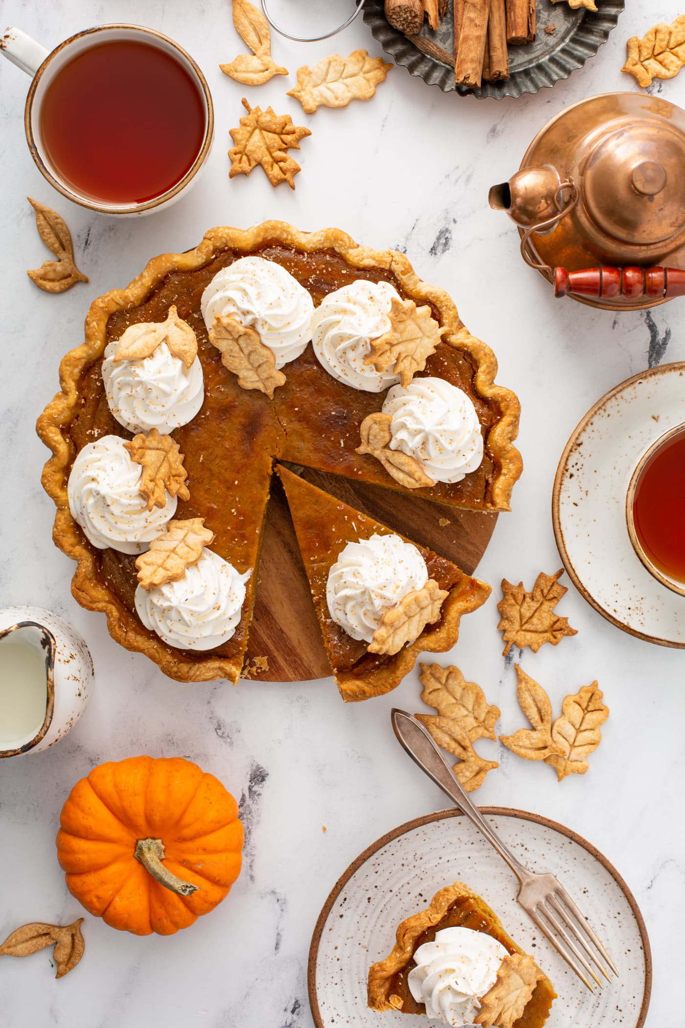 A photo of a pumpkin pie topped with piped whipped cream and stamped pie crust leaves taken from above with a slice pulled out.