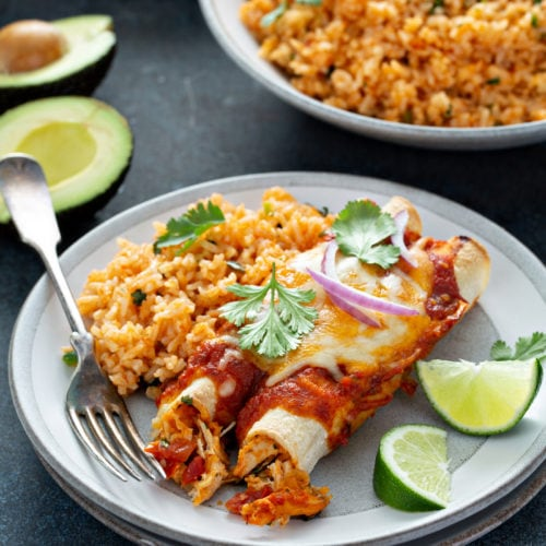 A serving plate with two enchiladas, Spanish rice, and two lime wedges. Cilantro leaves are sprinkled on top of the enchiladas. There is a bowl of Spanish rice and an avocado that is cut in half in the background.
