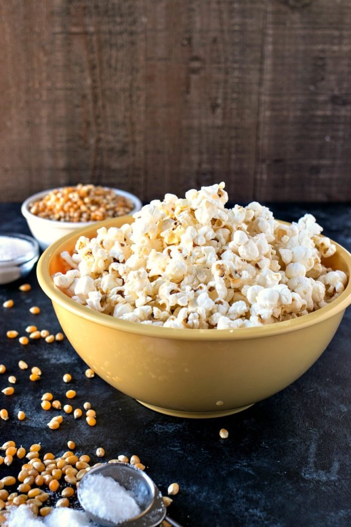 A big yellow bowl of Salt & Vinegar Popcorn with kernels on the side.