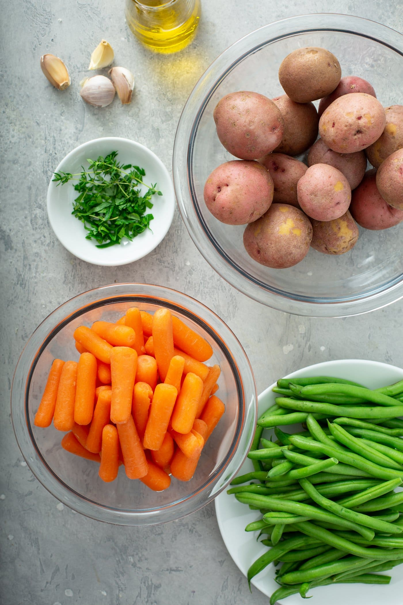 Bowls containing red potatoes, baby carrots, fresh green beans, and fresh green herbs.