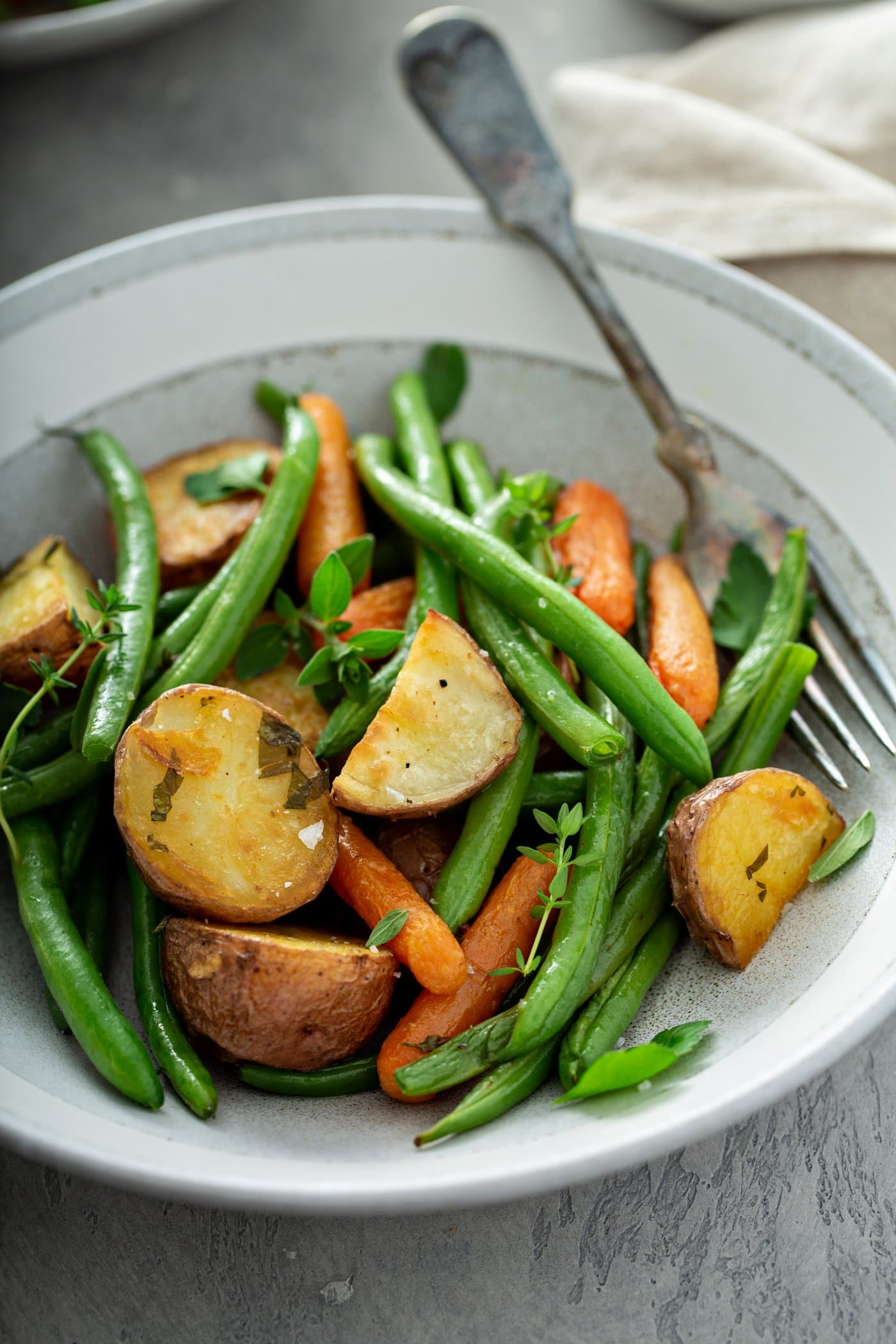 A plate filled with roasted red potatoes, baby carrots, and fresh green beans. A fork is resting next to the roasted vegetables.