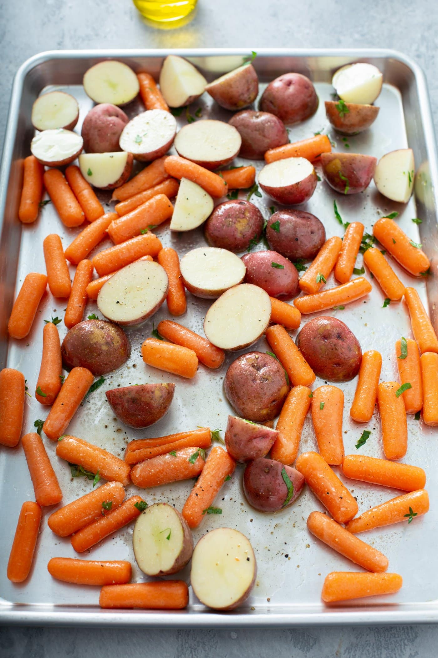 A sheet pan containing red potatoes that are cut in half and baby carrots.