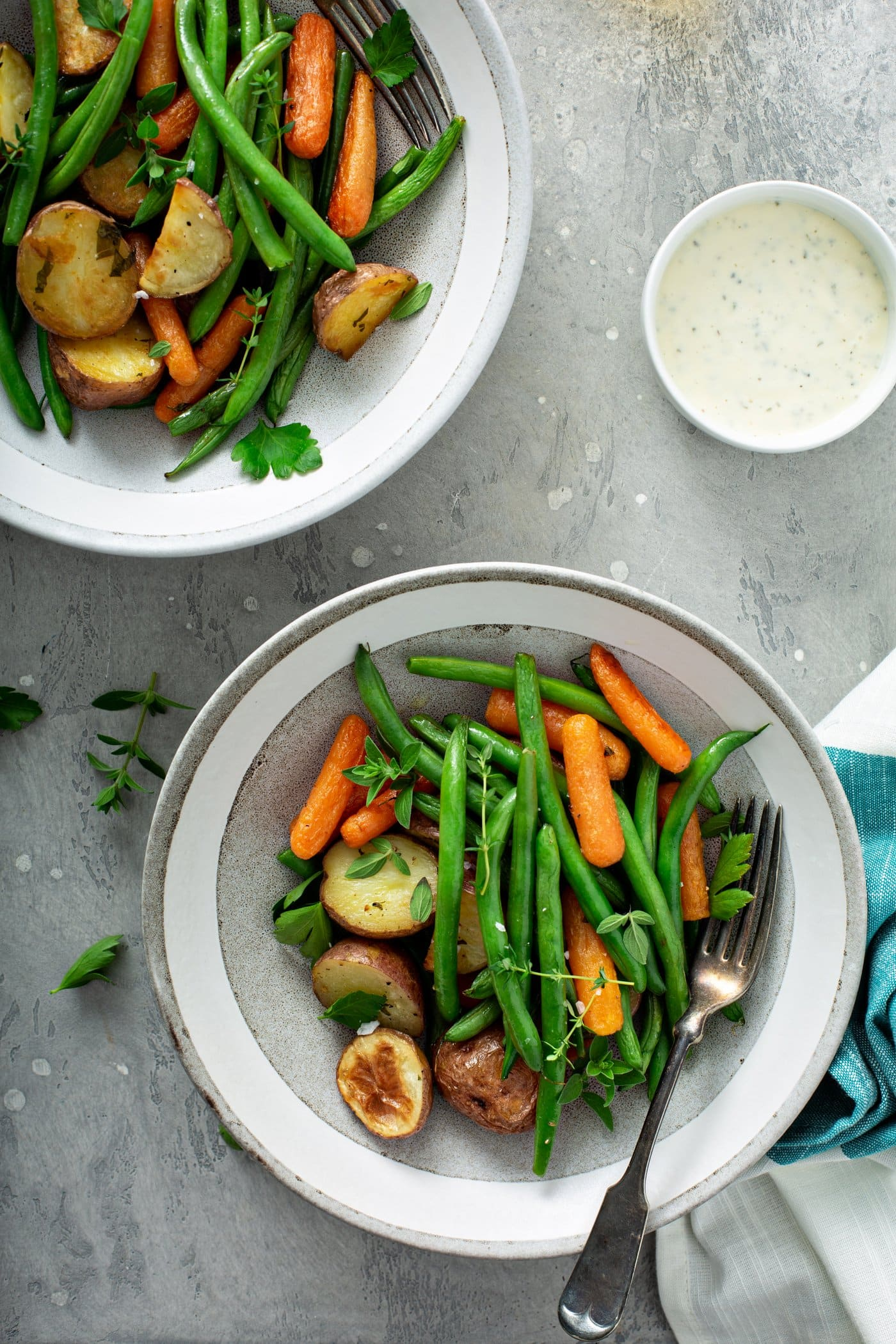 Two dinner plates filled with garlic herb roasted potatoes, carrots and green beans. Fresh parsley and thyme are sprinkled on top and on the table. A napkin is next to one plate, and a small bowl of salt is in the right corner.