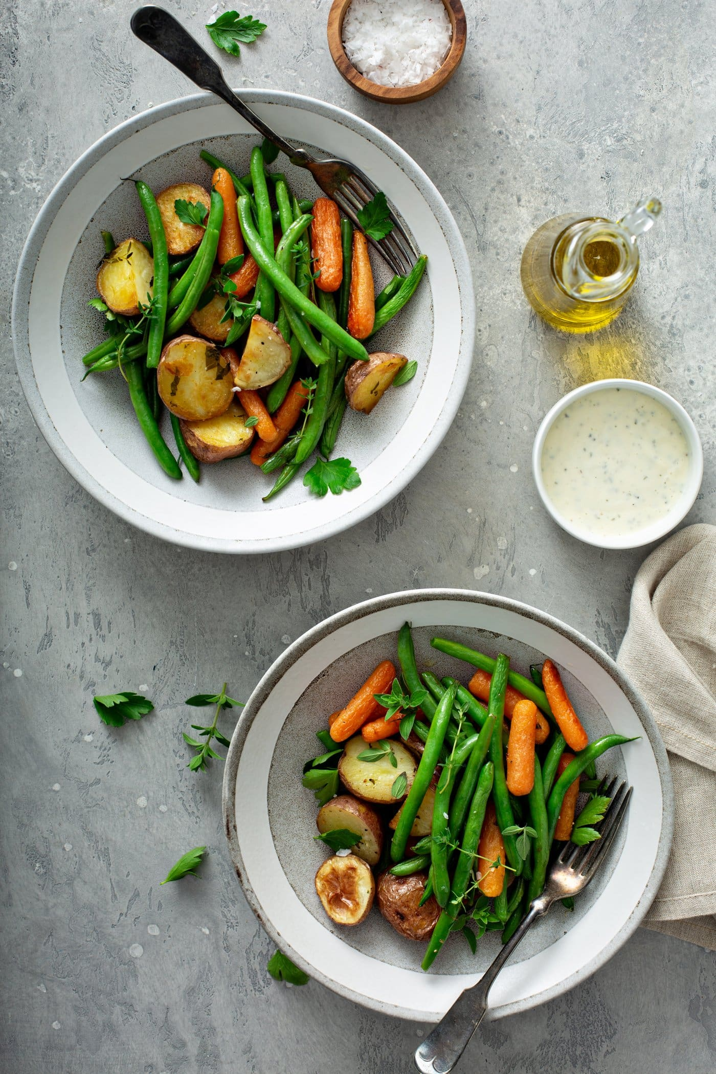 Two dinner plates filled with garlic herb roasted potatoes, carrots and green beans. Fresh thyme and parsley are sprinkled on top. A small container of sauce, a glass container of oil and a napkin are on the table next to the vegetables.