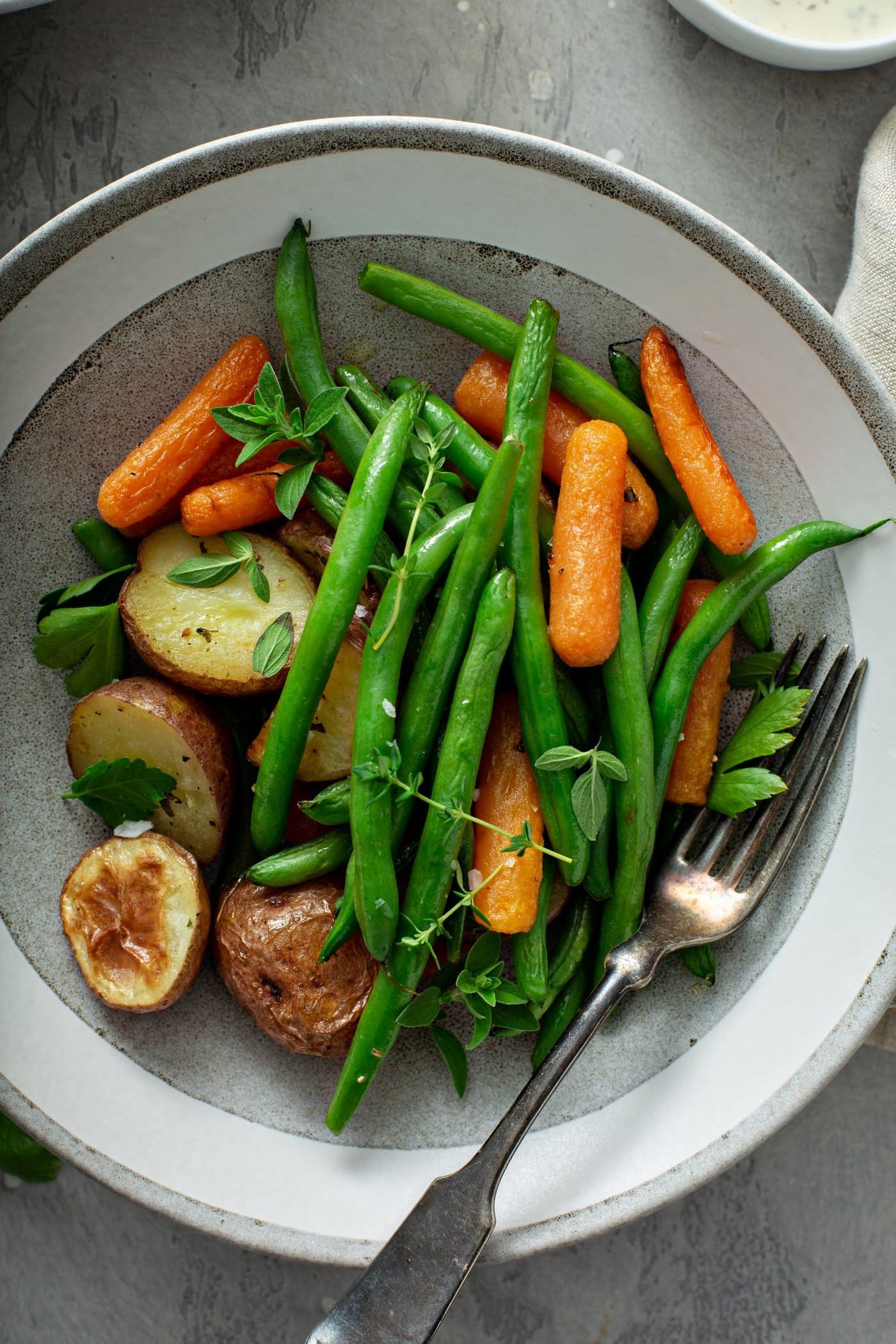 A dinner plate with roasted potatoes, carrots, and green beans. The vegetables are sprinkled with fresh herbs and a fork is resting on the plate next to the vegetables.