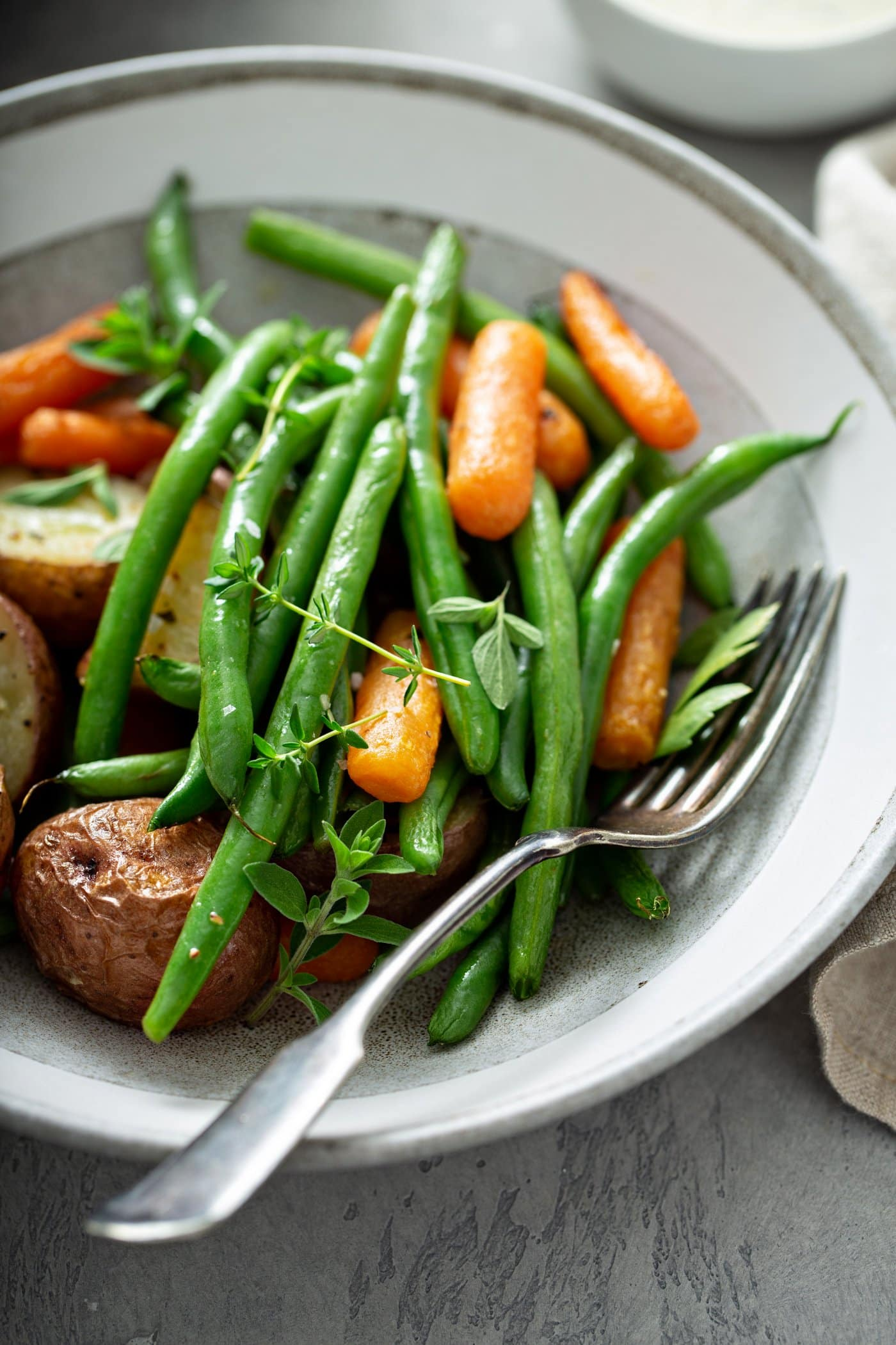 A dinner plate of garlic herb roasted potatoes, carrots and green beans. A fork is laying on the plate next to the vegetables, and they are topped with fresh thyme.