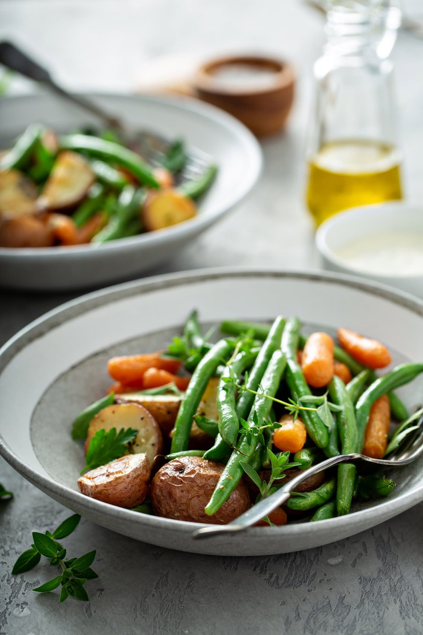 A dinner plate filled with garlic herb roasted potatoes, carrots, and green beans. A fork is resting next to the vegetables. A Serving platter of roasted vegetables, a small bowl of salt, a glass container of oil and