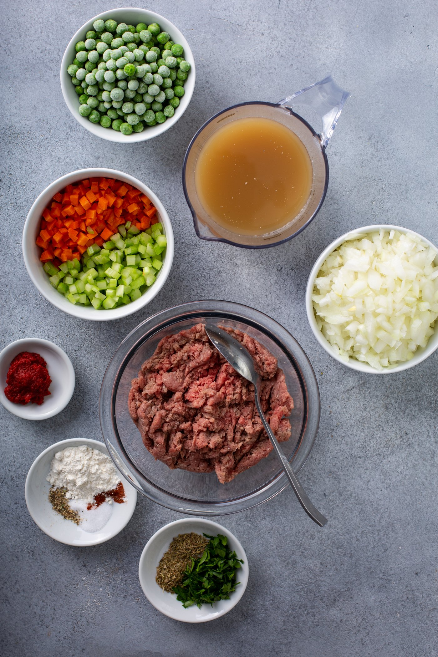 A table top with containers of ground beef, onions, chopped red and green peppers, spices, peas, and broth.