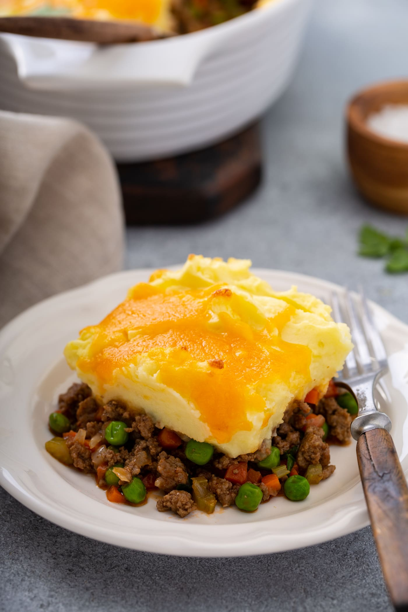 A serving of shepherd's pie on a white plate with a fork beside it. There is a napkin and a casserole dish in the background.