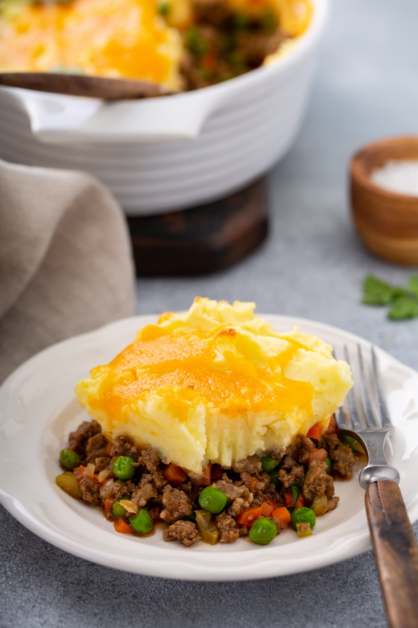 A serving of shepherd's pie with carrots, peas and ground beef for filling, topped with mashed potatoes and melted cheese. There is a fork resting on the plate and a napkin and a small container of salt next to it.