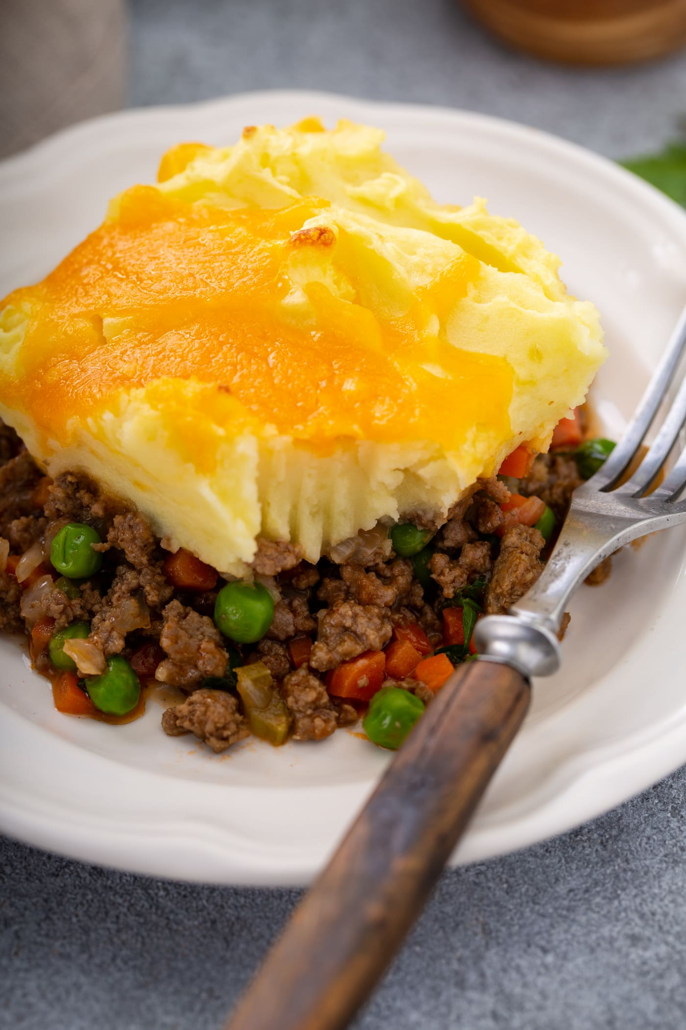 A serving of shepherd's pie on a white plate with a fork resting beside it. You can see the rich ground beef and vegetable filling, the mashed potatoes on top, and the yellow melted cheddar cheese topping it all.