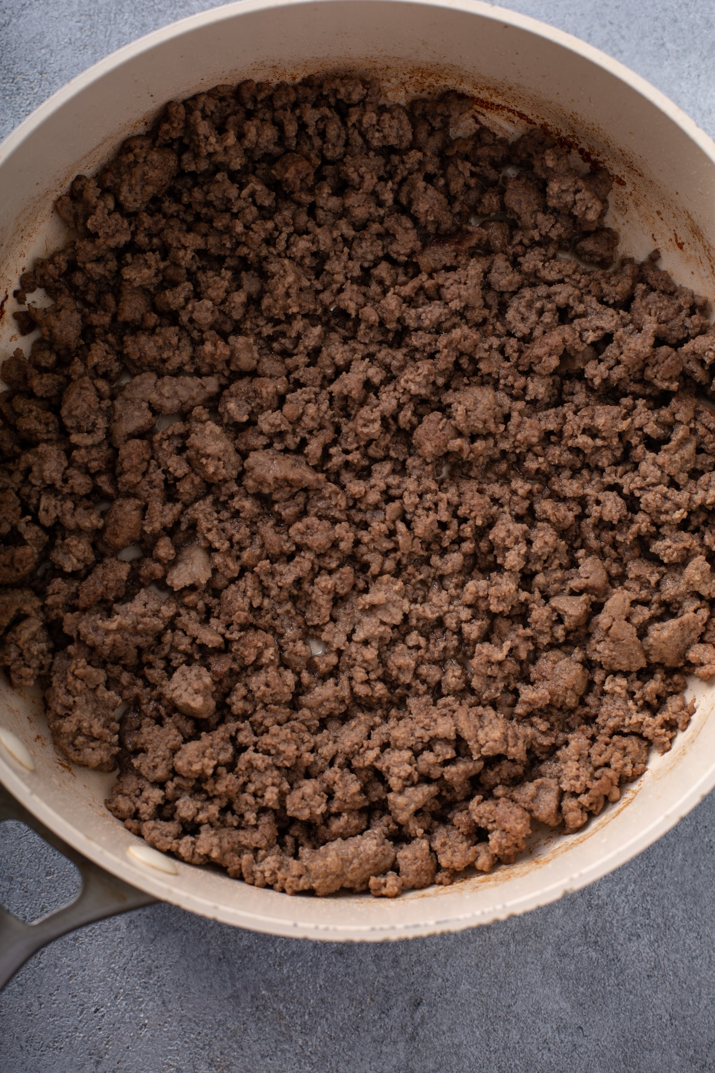 A casserole dish containing browned ground beef.