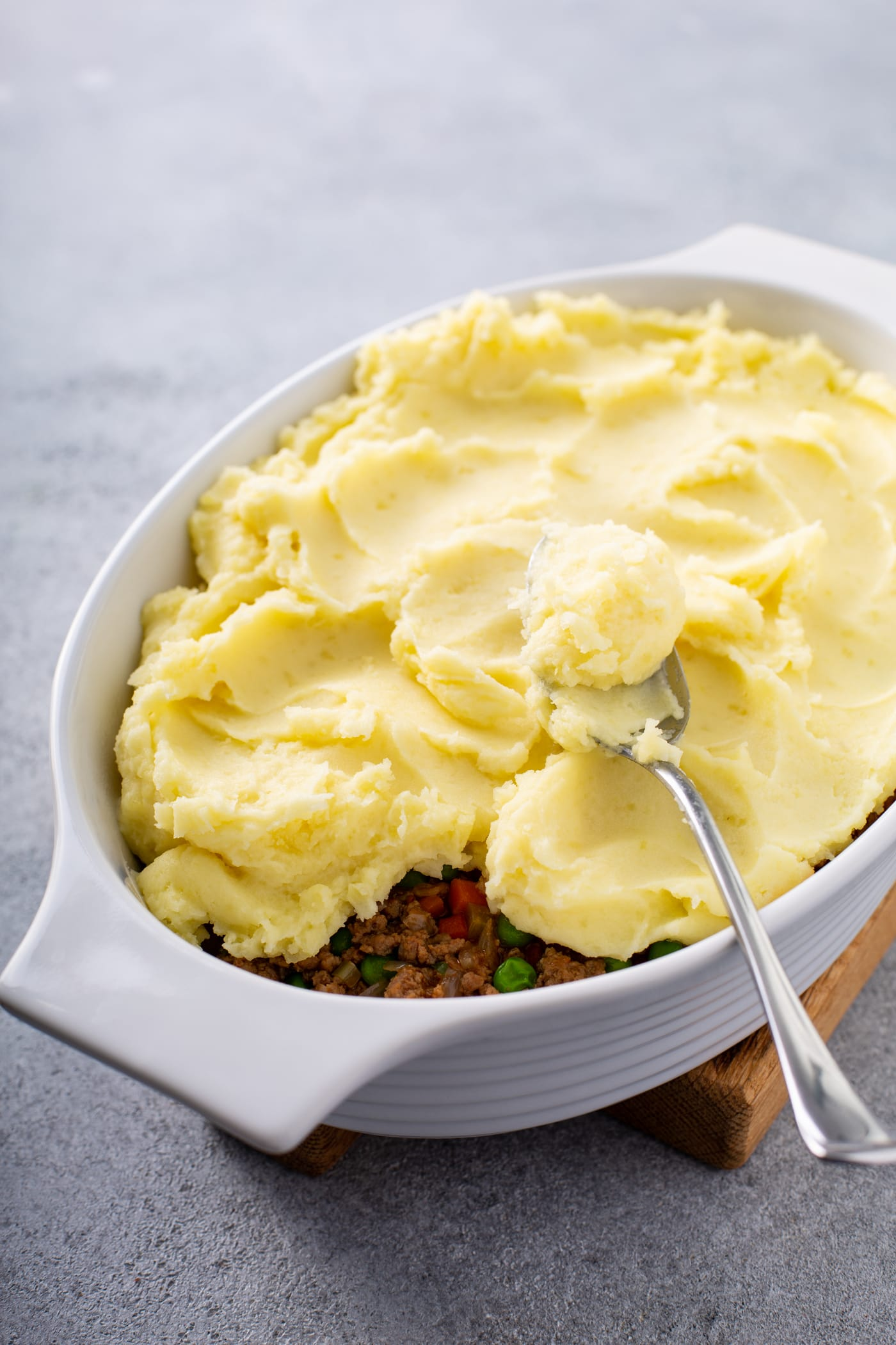 A casserole dish filled with shepherd's pie filling and topped with mashed potatoes. There is a spoon resting on top.