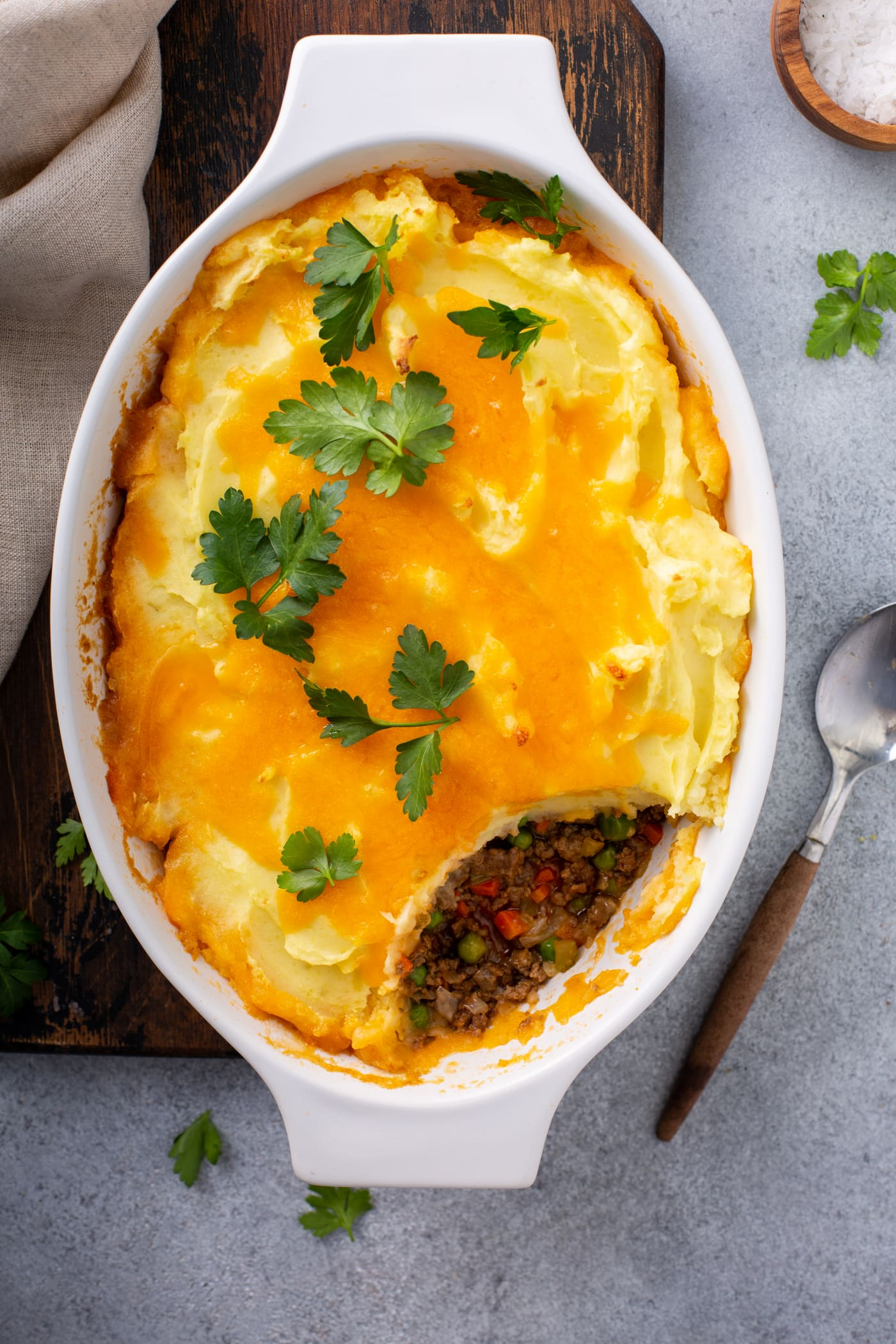 A casserole dish of shepherd's pie. A serving has been removed so you can see the ground beef, carrots and peas in the filling. It is topped with mashed potatoes and melted cheese with a few parsley leaves on top.