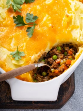 A casserole dish containing shepherd's pie with one spoonful removed and the serving spoon resting in the dish. You can see hamburger, carrots, and peas in the pie and it is topped with mashed potatoes, and melted cheddar cheese. There is a few parsley leaves on top.