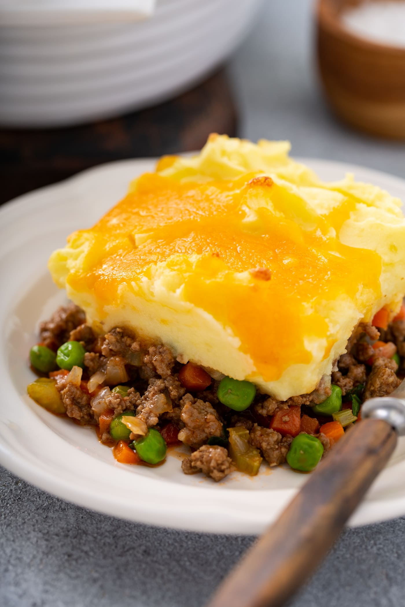 A serving of shepherd's pie on a white plate. there is a fork resting next to it on the plate.
