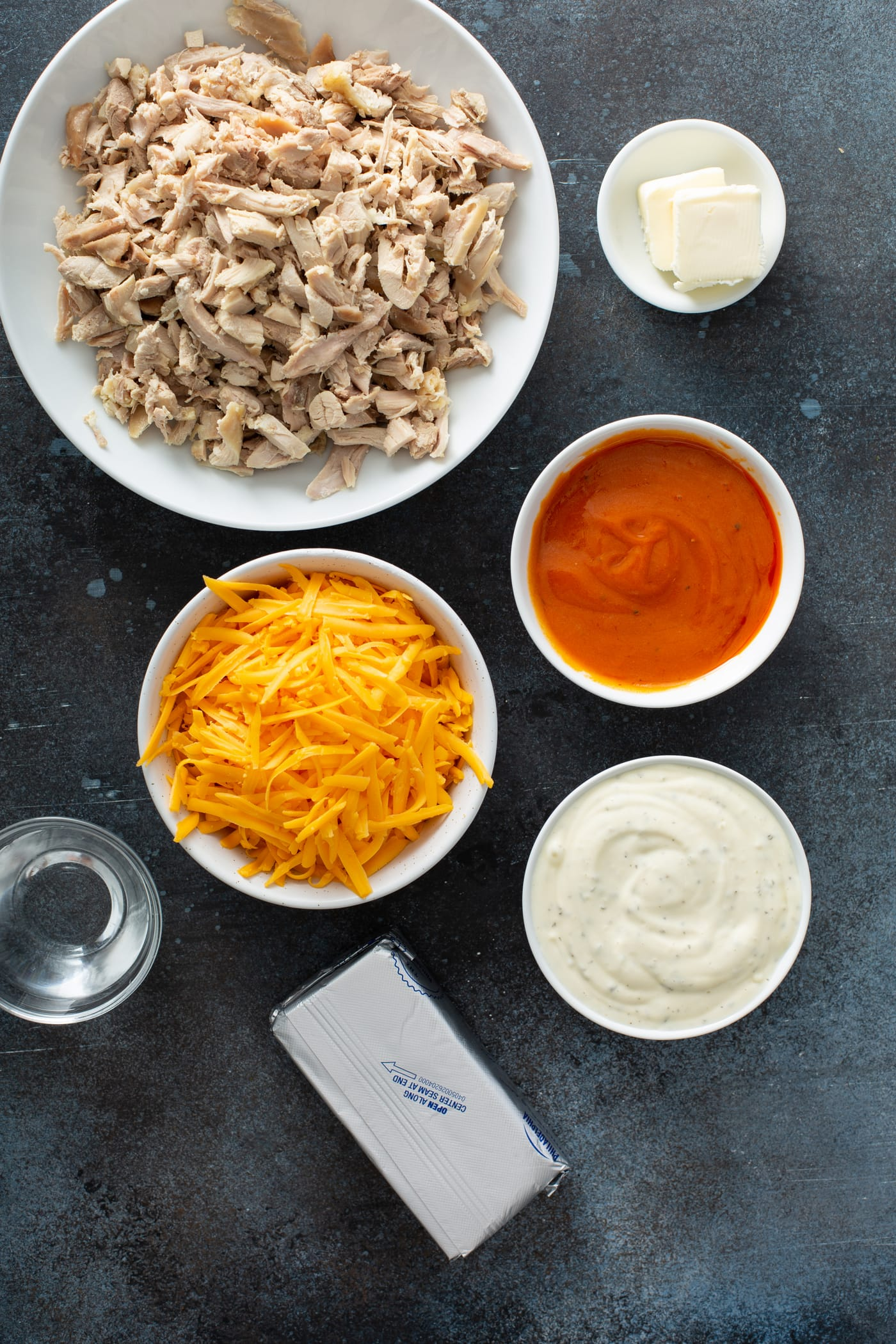 Small containers of ingredients for buffalo chicken dip. There is shredded cheese, shredded chicken, cream cheese, buffalo sauce, ranch dressing, and water.